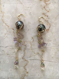 Elegant handmade freshwater peacock pearl, ametrine gemstone, peridot and Swarovski crystal 14k gold filled dangle earrings, made by ZahidasJewellery Beautiful wire wrapping with these unique statement earrings, these give off lovely golden, lime green and purple hues with movement! Black Pearl Earrings, Peridot Earrings, Dangly Earrings, Pearl Jewelry, Statement Earrings, Cluster Earrings, Handmade Jewelry Designs, Earrings Handmade, Handmade Jewellery