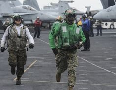 GULF OF OMAN (June 13, 2013) – Gunnery Sgt. Enel Laborn (right) and Lance Cpl. Eric Saldana, assigned to the Death Rattlers of Marine Fighter Attack Squadron (VMFA) 323, rush to their stations during flight operations aboard the aircraft carrier USS Nimitz (CVN 68). Nimitz Strike Group is deployed to the U.S. 5th Fleet area of responsibility conducting maritime security operations and theater security cooperation efforts.