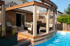 """A curved lounge zone overhangs the pool with a fire pan, three waterfalls and a retractable awning!  Luxury.  From """"Decked Out"""" project """"The Waterfall Deck"""".  Deck Design by Paul Lafrance Design."""