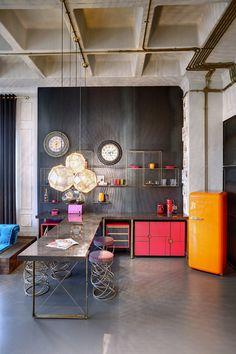 Estúdio com estilo industrial com alguns móveis coloridos