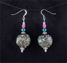 Vibrant earrings. Teal green, pink, and black lampwork glass bead earrings.   *Beads: Lampwork and glass beads   *Earwires: Sterling silver   *All other metal is silver plated.   *Length: 1.75 inches (from the bottom of the ear hook)   *Width: 0.9 inches (at the widest part)   *Handcrafted in Fayetteville, Arkansas