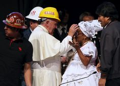 """Pope Francis, wearing a helmet, blesses a woman as Bolivian President Evo Morales (R) looks on, during a World Meeting of Popular Movements in Santa Cruz, Bolivia, July 9, 2015. Pope Francis on Thursday urged the downtrodden to change the world economic order, denouncing a """"new colonialism"""" by agencies that impose austerity programs and calling for the poor to have the """"sacred rights"""" of labor, lodging and land. REUTERS/Alessandro Bianchi  - RTX1JSW8"""