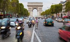 A man walks amid traffic on the Avenue des Champs-Elysees in Paris.