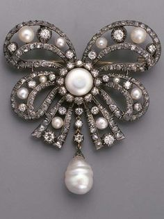 AN ANTIQUE PEARL AND DIAMOND BOW BROOCH. Designed as a central button-shaped pearl within single-cut diamond surround to the openwork pearl and old-cut diamond bow suspending a (later) cultured pearl and diamond three-stone pendant, mounted in silver and gold, circa 1880.