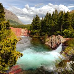 a turquoise waterfall-Glacier National Park in Montana - the park's Swiftcurrent Pass