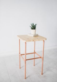 Designed and made in Brighton, UK by Little Deer this pine bedside table features beautiful thin copper legs. This piece is designed to sit next to your bed to store your phone, watch, books, alarm clock or reading glasses etc. The top features varnished pine with rounded edges and the shelf that sits halfway up the legs is the perfect to keep a stack of magazines or books on. Each bedside table is made to order from industrial copper pipes and fittings. Once finished your table will be…