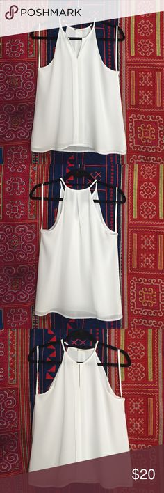 Flowy White Tank Really cute white top that pairs well with everything! Never worn because it is just a little too big on me, so hopefully someone else can love this top for me! There's a small clasp at the front near the neck that allows the top to be more open or covered up (see photos). This top is from a boutique so there is no size tag, but it fits like a size S. Tops
