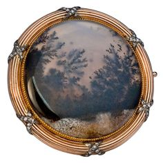 An impressive moss agate brooch by Fabergé, workmaster Henrik Wigstrom. The pink gold, ribbon tied, reeded frame is in the Neo-Classical taste of Louis XVI period. The silver ribbons are set with tiny rose-cut diamonds. The moss agate plaque has tree-form inclusions resembling a forest.