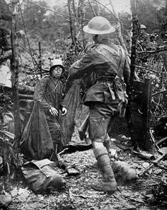 A very young German soldier climbs out of a trench and surrenders himself to a Scottish soldier