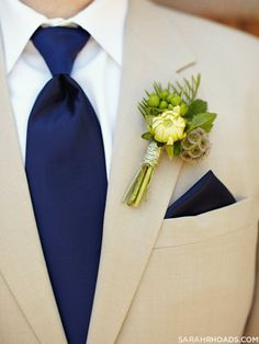 Men's tan suit with navy tie