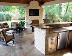 Stone countertops, bar, fireplace and flooring are a natural for this outdoor space