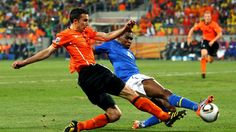 PORT ELIZABETH, SOUTH AFRICA - JULY 02: Juan of Brazil tackles Robin Van Persie of the Netherlands during the 2010 FIFA World Cup South Africa Quarter Final match between Netherlands and Brazil at Nelson Mandela Bay Stadium on July 2, 2010 in Nelson Mandela Bay/Port Elizabeth, South Africa. (Photo by Richard Heathcote/Getty Images)