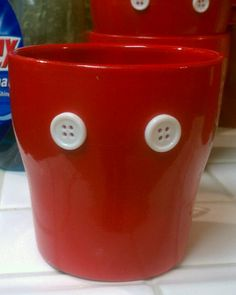 Spray paint a small ceramic  flower pot red, allow to dry, glue gun bottons.  I used these as utensil holders.