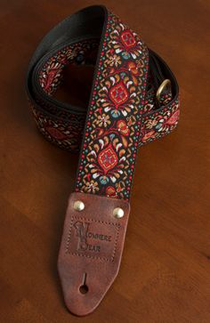 Red/Bronze/Black Guitar Strap. Each Nowhere Bear strap has hand crafted leather ends stamped with the Nowhere Bear logo and is backed with