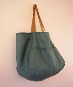 Un grand sac cabas en toile de lin bleue denim avec anses en cuir.  Sa taille généreuse fait de ce cabas un compagnon parfait pour tous les