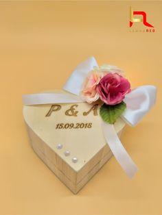 Cutie din lemn pentru verighete, in forma de inima, avand gravate initialele mirilor si data nuntii. Decoratiunile de pe cutie pot sa difere in functie de preferintele mirilor.