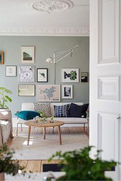 Persoonlijke verzameling en witte wandlamp boven de bank - bekijk en koop de producten van dit beeld op shopinstijl.nl