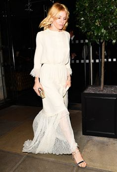 Sienna Miller wears a white Michael Kors dress with lace detailing and metallic accessories