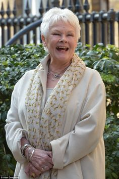Laughing it off: Dame Judi Dench was in great spirits as she arrived to unveil a sculpture...