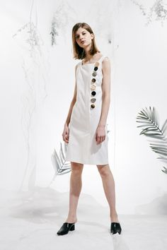 <p>Above the knees length sleeveless dress. Slit in the front hem. Button decorated detail. Color:white. About me:56% viscose,37% chinlon,7% spandex</p>