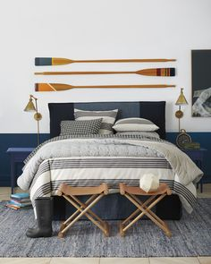 We love the nautical decor in this masculine bedroom with leather stools, a slipcovered bed, and a blue rug. Slipcovered Headboard, Deco Marine, Striped Bedding, Coastal Bedrooms, Neutral Bedrooms, White Bedrooms, Coastal Living, Above Bed, Headboards For Beds