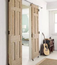 ~ DIY ~Instead of buying an expensive barn door track kit, make one yourself. Fifty-eight dollars worth of hardware—including casters and plumbing pipes—transformed two salvaged doors into a barn-style entry. Salvaged Doors, Old Doors, Barn Doors, Sliding Doors, Repurposed Doors, Wooden Doors, Entry Doors, Patio Doors, Sliding Cupboard