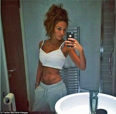 Abs-olutely fabulous: Michelle Keegan flaunted her toned and tanned abs in a skimpy white crop top as she posed in her hotel mirror for a ra...