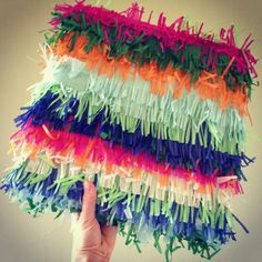 Make pinata wrapping paper by fringing tissue paper with scissors and pasting onto some brown Kraft paper as a base.