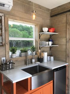In the kitchenette is a stainless steel apron sink and under counter refrigerator.