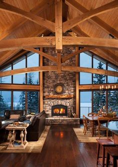 "Rustic living room area with vaulted ceiling, great ""stretch"" floor-to-celing windows, and lakefront view."