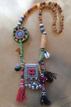 ETHNIC TREE: Tribal art necklace whose base is made of semi-precious stones. The embroidered flower is Rabari Indian. The centerpiece is vintage Yemeni and the tassels are vintage Uzbek. The cowry shell and the nut come from a Nepali medicine necklace. The triangular glass bead is an Afghani amulet. This necklace is entirely handmade and a one-of-a-kind item.
