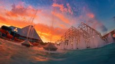 """What a sunset! Photographer Tom Bricker captured this lovely shot of Future World at Epcot, which shows the amazing """"upside-down"""" fountain that highlights the area, and behind it, the Imagination Pavilion."""