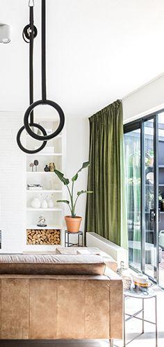 Deze stijlvolle woon- en tuinkamer zijn in de basis strak. Beide hebben ze een eigen basiskleur gekregen: de woonkamer wit en de tuinkamer zwart. Er is veel opbergruimte gecreëerd in beide ruimtes door kastenwanden. Zo is er aan beide kanten van de televisie en haardwand een lange kast gemaakt. Door bij de aankleding creatief te zijn met verschillende kunst, design- en vintage meubelen, krijgt de ruimte een artistiek uiterlijk.