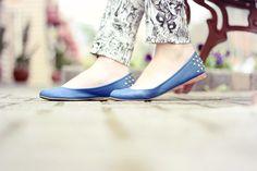 Look com calça estampada com caveiras suéter preto com lantejoulas e sapatilha azul