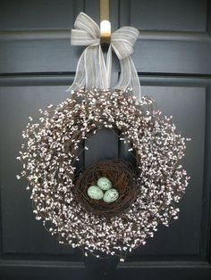 Love the contrast of the black door and the white wreath with the eggs providing just that little pop of color.
