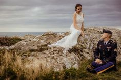 Bride and groom posing on rocks for a wedding picture.