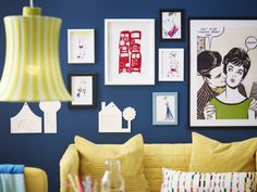 Colorful pictures on a dark blue wall above a yellow sofa
