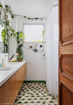 Banheiro com piso de ladrilho hidráulico e plantas pendentes.