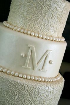 Love love love! Pearlescent fondant with hand-piped detailing, pearls, and monogram.