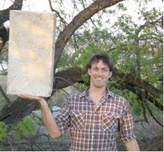 Holding up a lightweight Papercrete Brick, image by oneVillage Initiative