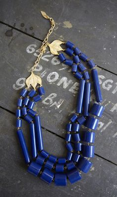 Triple strand of smooth, cylindrical resin beads in a lapis blue colour. 18k gold plated clasp and adjustable chain