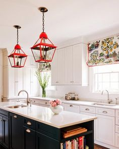 A pop of color in a simple black and white kitchen makes all the difference. Love the lighting!