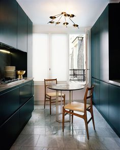 Flat in Paris (Saint-Germain-des-Prés) decorated by #Dimore (Britt Moran et Emiliano Salci) - Black and white kitchen with a Bethan Laura Wood table, 2 chairs from the 50s, light from Gino Sarfatti (#Arteluce)