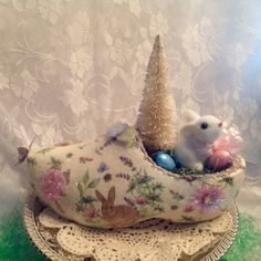 A vintage wooden shoe, decorated and embellishedfor your Easter table! Handpainted, decoupaged and embellished with butterflies, flowers and glitter. Finally I added the tree, some small eggs, a sweet bunny and a bow.  This piece measures approximately 12 long by 9 tall.