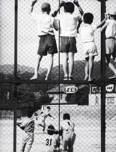 Eliot Elisofon, Children watching a baseball game through a fence,  Kyoto, Japan, 1961.