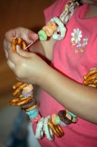 """Edible snack necklace.  Great for """"movie night.""""  Make it, then munch during the show.  Materials: twine, any circular cereal, any circular cookies, preztles, gummy circles.  Enjoy!"""