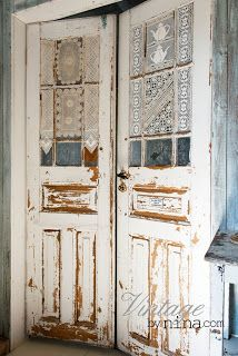 Love these old doors with the doilies adhered to the glass panes.