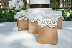 Wedding favors- in brown paper bags- adorned with paper lace doilies and tied with ribbon. Positively elegant!