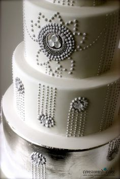 White wedding cake with silver art deco accents. Such a cool design!