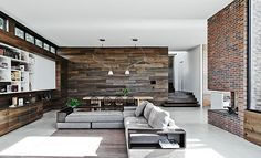 Large living area and dining space with reclaimed wood walls and concrete floor - Decoist
